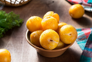 Yellow ripe plums on wooden table