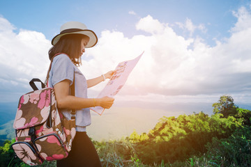Woman traveler seeing on map with mountain view and cloudy sky in vintage tone
