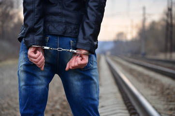 Girl in handcuffs on the background of a railway track