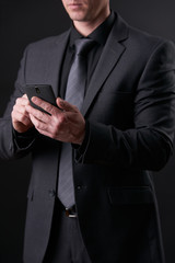 Portrait of a young Successful businessman in black, trendy, modern and stylish suit using smartphone on isolated black background