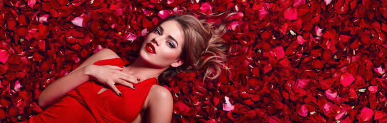 Valentines Day. Loving girl. The girl in a red dress lying on the floor in the petals of red roses. Background of red rose petals. Red lipstick on the lips from the beautiful girl.