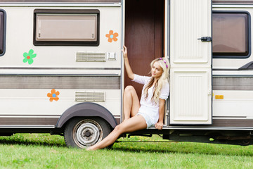 Young and beautiful hippy girl sitting on trailer. Holiday, journey, vacation concept.