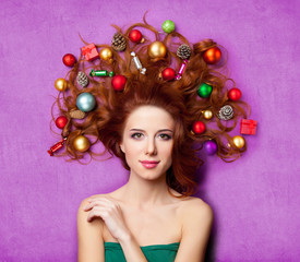 beautiful young woman with gifts, candies, baubles and cones in her hair lying on the wonderful purple background