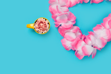 beautiful hawaiian lei and rose in yellow cup on the wonderful blue background