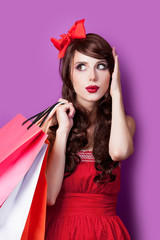 photo of beautiful young woman with shopping bags in santa claus hat on the wonderful purple background