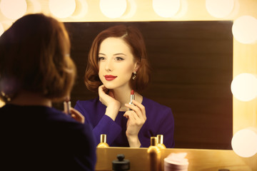 photo of beautiful young woman holding her lipstick near the window with lights