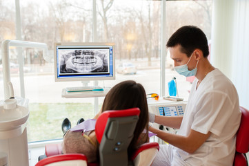 The dentist tells the patient about the condition of the teeth.