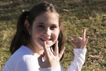 Little girl doing yoga meditating in park