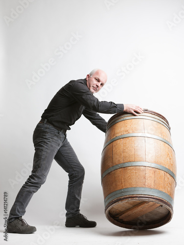Man Moving A Large Oak Wine Or Beer Barrel Stock Photo And Royalty