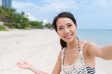 Woman holding camera to take selfie in sand beach in sunny day