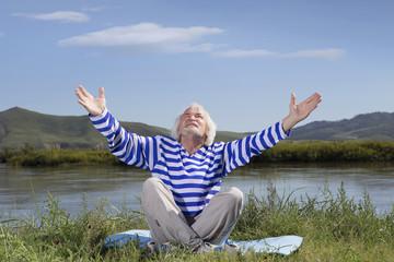 Elderly man sitting on a river bank