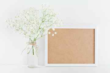 Mockup of picture frame decorated flowers in vase on white working desk with clean space for text and design your blogging.
