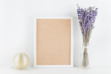 Mockup of picture frame decorated lavender flowers in vase on white working desk with clean space for text and design your blogging.