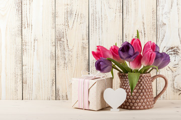 Fresh tulips, white heart and gift box