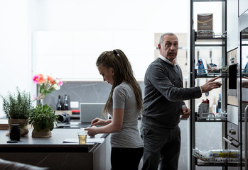Father and daughter preparing a meal in a kitchen