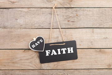 "Blackboards with text ""Have faith"" on wooden background"
