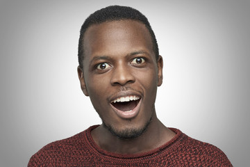 Close-up portrait of African American man wearing casual red sweater having amazed and surprised look, opening mouth widely. Headshot of surprised joyful black student shocked with unexpected success