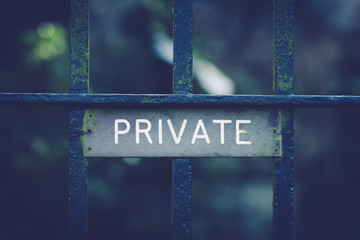 Private sign on wrought iron gates with an antique filter applied to the image useful for privacy or security concepts