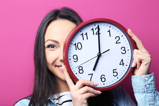 Young woman holding a clock on pink background