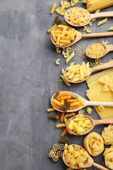 Different kinds of pasta in wooden spoon on grey table