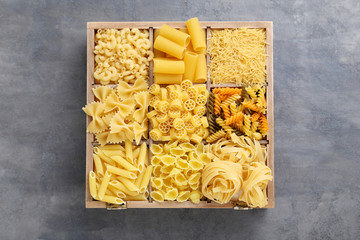 Different kinds of pasta on grey wooden table