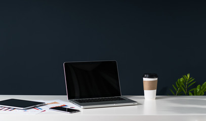 Nearby is a tablet computer, a smartphone, paper graphics, a cup of coffee. In the background a dark wall.