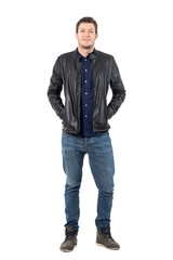 Relaxed man in jeans and leather jacket smiling at camera with hands in pockets. Full body length portrait isolated over white studio background.