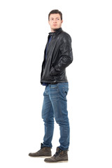 Side view of young man in leather jacket and jeans looking back over the shoulder. Full body length portrait isolated over white studio background.