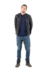 Young man in leather jacket and jeans with hands behind back and titled head. Full body length portrait isolated over white studio background.