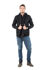 Confident young casual male in hooded black winter jacket and jeans. Full body length portrait over white studio background.