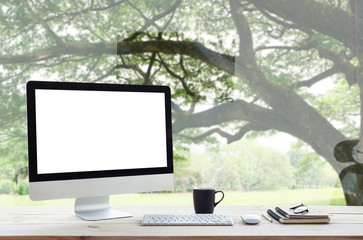 desktop computer on work table and nature background