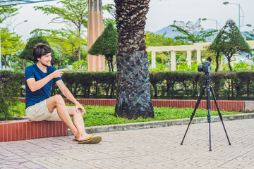 Young man blogger records video in front of the camera in the park