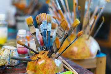 artist brushes in the stand on blurred background