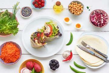 Healthy wrap sandwich with fresh vegetables, chick peas, eggs, olive oil and soy sauce and wrap ingredients on a white table. Top view.