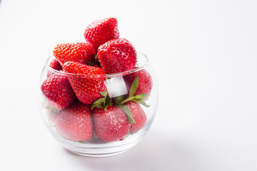 fresh strawberries in a glass round shape on white background
