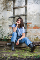 Young woman sitting on a ladder on the farm