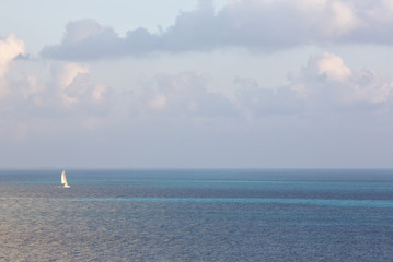 White sailboat in the middle of the ocean. Simplicity. Beautiful wallpaper.