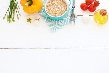 Brown rice, bell pepper, cherry tomato, baby eggplants, spring onions, garlic and olive oil on a white table. Healthy dinner background. Space for text.