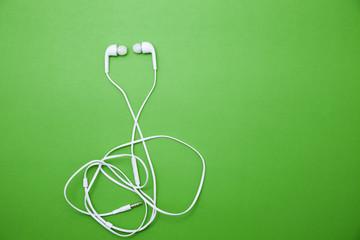 earphone on green paper background.