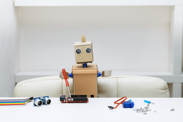 robot sits at a table and holds a screwdriver lying next to a robot parts for assembly