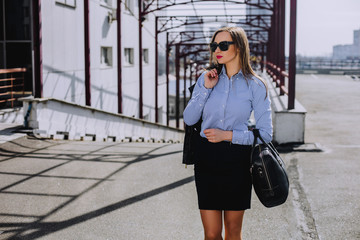 Stylish business woman walking around the city holding a suitcase. Modern summer clothes for a business lady, shirt and black skirt.