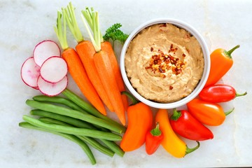 Hummus dip with a variety of fresh vegetables, above view on a white marble background