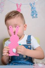 smilling boy making bunny for easter