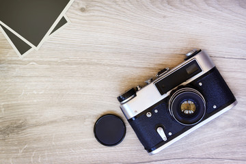 Old retro camera and photos on a wooden background.