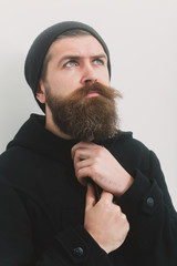 bearded serious brutal caucasian man in black jacket and hat