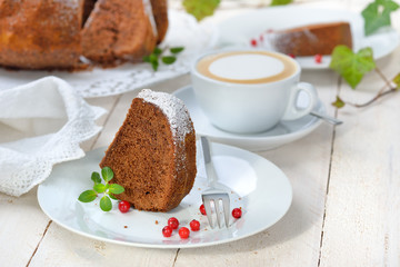 Schoko-Guglhupf mit  Zartbitterschokolade mit einer Tasse Cappuccino serviert - Freshly baked ring-shaped cake with chocolate, so called Gugelhupf in Austria and Germany, served with a cup of coffee