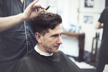 Smiling man in barbershop watching the process of hair cutting