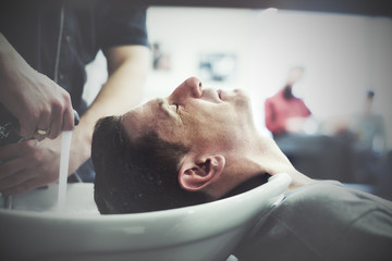 Man in a hairdresser enjoys the process of washing his head