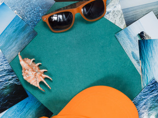 Sunglasses, shell, cap, and pictures with the image of the sea on wooden surface