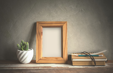 mock up blank photo frame with cactus flower on bookshelf.